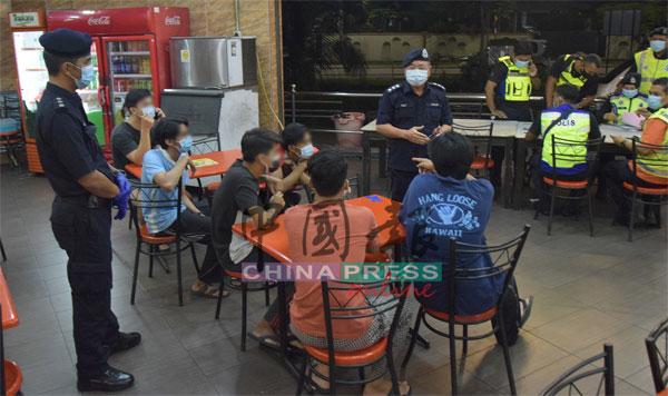 马永来(站者左2)询问6名因没扫二维码的学生,为何违反标准作业程序。