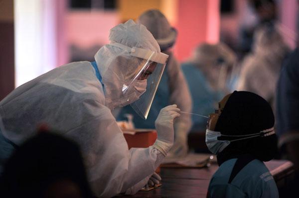 卫生局官员为北根国小一校学生进行冠病检测。