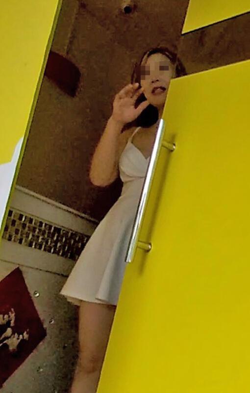穿着低胸白色连身裙,按摩女主动开门招揽路过的男顾客。