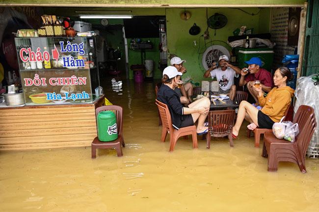 越南中部顺化市周六淹水,居民在一间淹水的小食店内休息。(法新社)