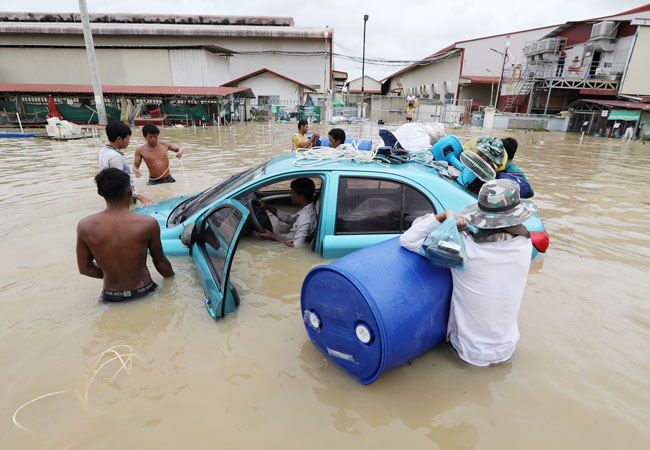 周五在柬埔寨首都金边郊区,一辆轿车被洪水淹没,民众帮忙救出司机。(欧新社)