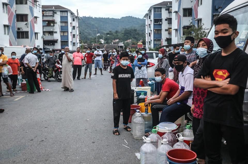 当地居民皆戴好口罩,排队拿水。