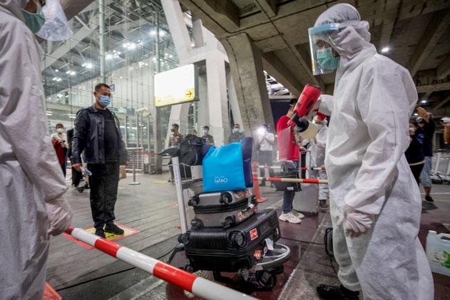机场卫生人员为中国旅客的行李消毒。(美联社)