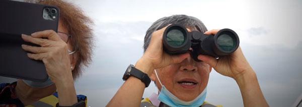 老爷爷用望远镜,希望清楚看到孙子样子。
