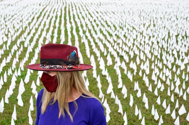 """美国艺术家苏珊娜周二站在华盛顿州肯尼迪纪念体育场的数千支白旗前,悼念美国死于新冠肺炎的患者。据报导,苏珊娜近日发起一场名为""""这怎么会发生在美国?""""的艺术装置活动,插白旗悼念逝者,预计完成时将有24万支白旗遍布草地。(美联社)"""