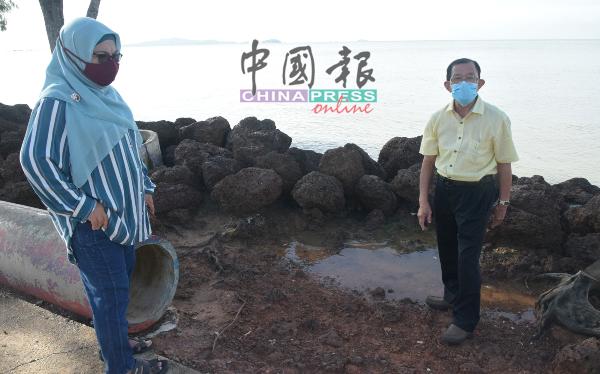 林祥和(右)与玛哈妮巡视以铁锈石充作的防浪石,无法阻止海水倒流至住宅区。