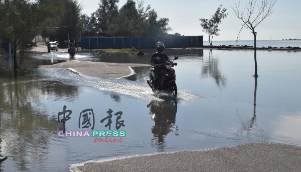 居民骑摩哆涉水而过。