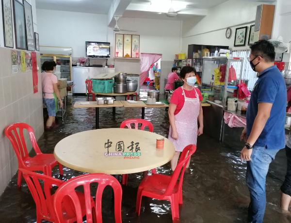 谭宝莲(左)向谢守钦反映素食店淹水的问题。