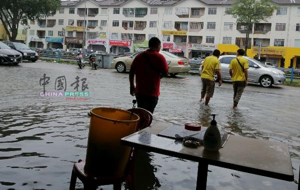 路面淹水,顾客用餐后,涉水而过。