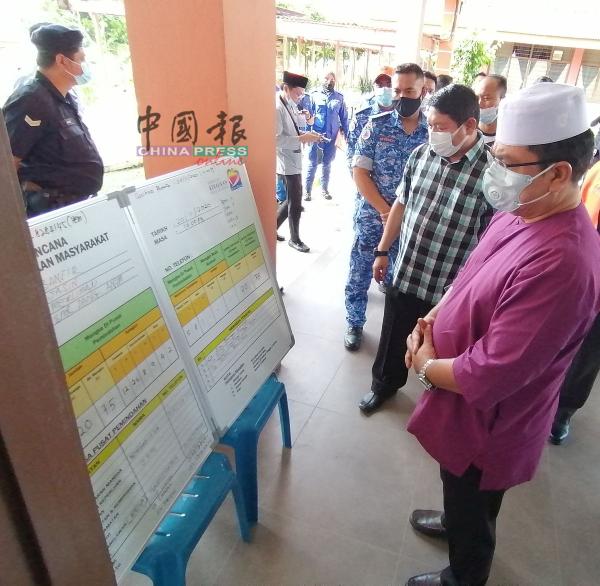 甲首长(右)通过告示板,了解当阿浓国中疏散中心的灾民数据与情况。