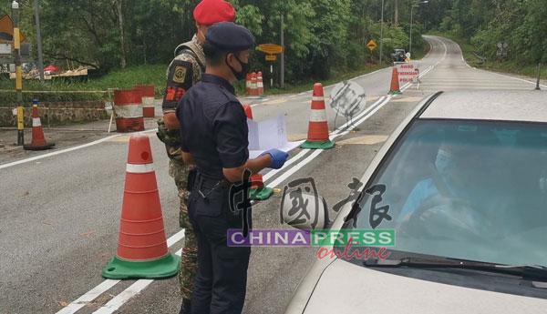 苏克里(左)要驾驶人士出示函件,并查证符合通关理由后才可过关。