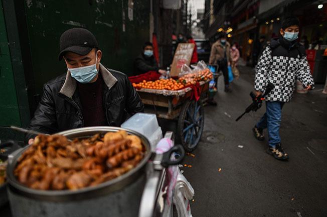 中国湖北武汉一条小巷内,小贩周五戴着口罩售卖食物。(法新社)