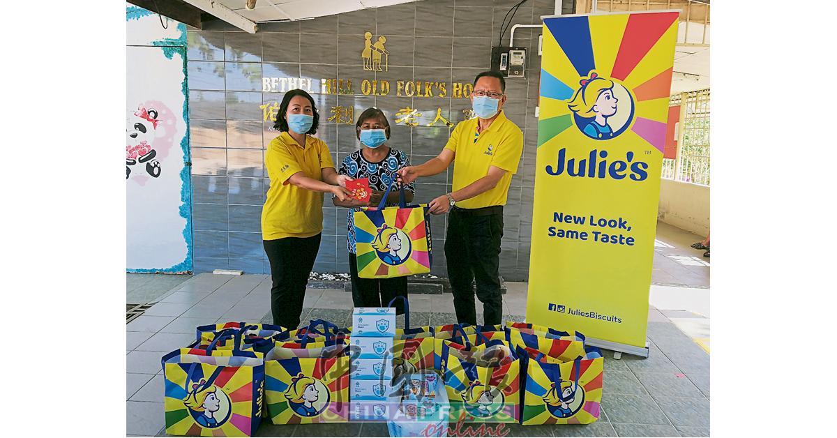 """陈爱娣(左)和刘来融(右),移交""""慈爱人间""""红包、防疫口罩、营养饮料包及Julie's饼干礼包,由罗金妹接领。"""
