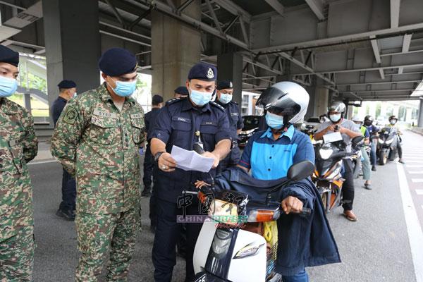 拉查里(中)和军人一同盘问途经警方路障的摩哆骑士,检查对方的信件。