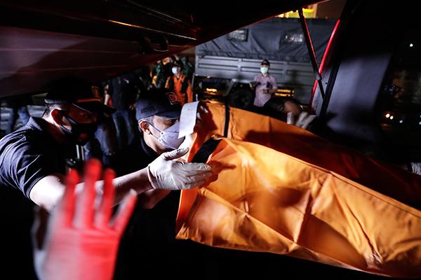 印尼天灾受害者辨认小组的官员用尸袋包裹可疑遗骸。(欧新社)