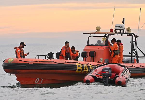 搜救人员乘船出海,在澜沧岛附近展开搜救行动。(法新社)