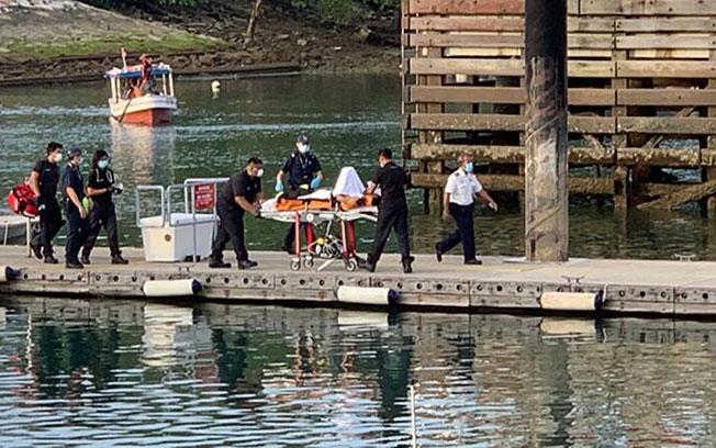 救护员在游艇俱乐部的码头用担架把死者送上救护车,他当时已昏迷不醒。(读者提供)