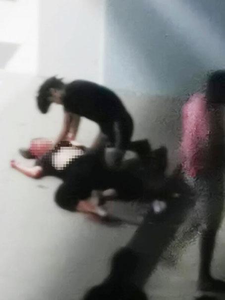 一名男子事发后按压着女子,疑在替她止血。(受访者提供)
