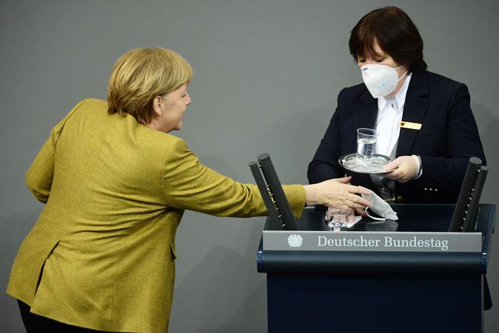 默克尔从清洁工人手上拿回口罩。