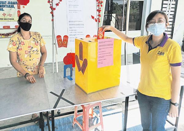 文德甲丹绒吉拉央残障中心准备捐献箱,方便民众投入红包或捐献,减少肢体接触,左起西塔及谢颖贤。