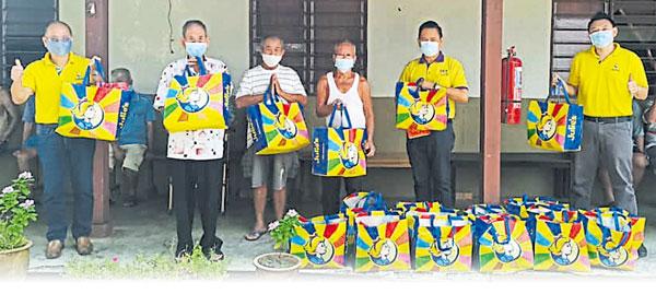 杨绪坚(右起)及林钦为移交红包及Julie's精美礼袋于马接峇鲁新村老人院的老人。左为林社安。