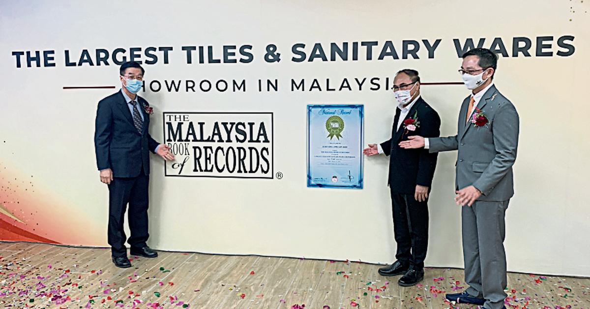 李卓荃(左起)、张发虎和洪桂平,在推介礼上展示全马最大瓷砖与卫生设备陈列室的大马纪录大全。