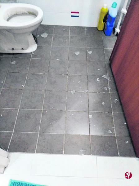 厕所灯罩掉落后,碎片洒一地。(受访者提供)