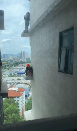 一名消拯员攀上5楼外墙靠近女子后,尽量游说和安慰她。