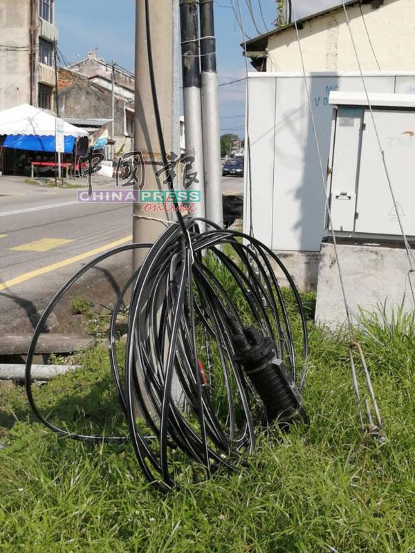 放在路边草堆的一大卷电缆。