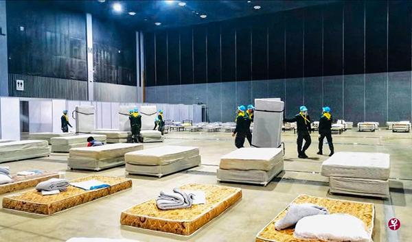 泰国政府在新冠肺炎疫情吃紧的地区加速兴建方舱医院。在清迈,当局出动士兵协助,单是运送和布置病床就是一大工程。(法新社)