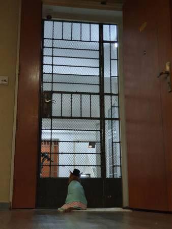 穿上马来传统服装的猫咪,坐在门口前,看似不想孤单呆着。