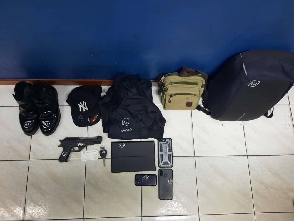 警方从嫌犯身上搜出仿真枪、子弹、手机、背包、服饰,以及一张警官名片。