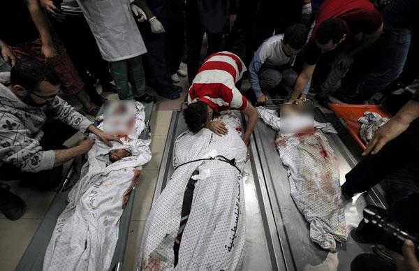 在以色列空袭中丧命的部分加萨民众,亲属抚尸痛哭。(法新社)