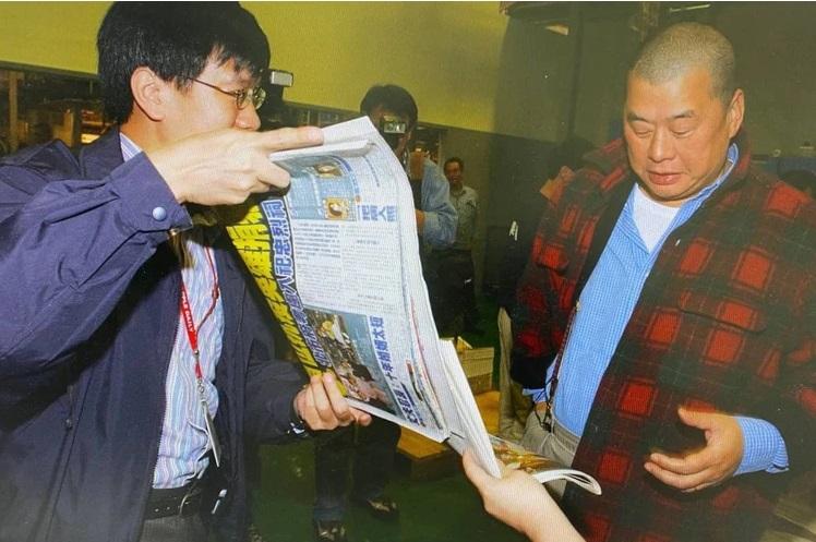 2003年5月2日凌晨,创办人黎智英在印刷厂检视刚印好的《台湾苹果日报》创刊号,图左为当时的总编辑陈裕鑫。