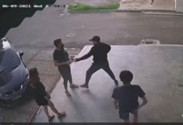 一對年輕男女在店前走廊交談時,3名男子突然圍上。(圖截取自視頻)