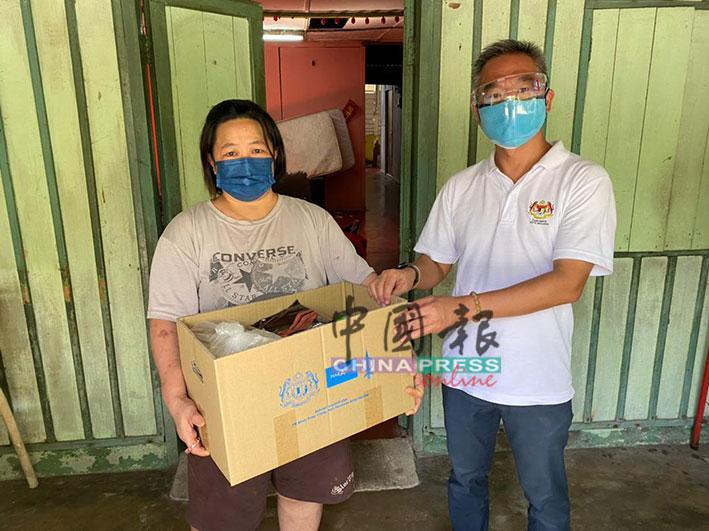 甲市区国会议员邱培栋(右起)移交白米及干粮给郑淑云。