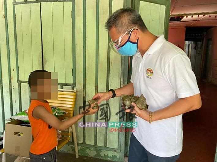 适逢端午节,邱培栋(右起)派发粽子给事主的孙子。