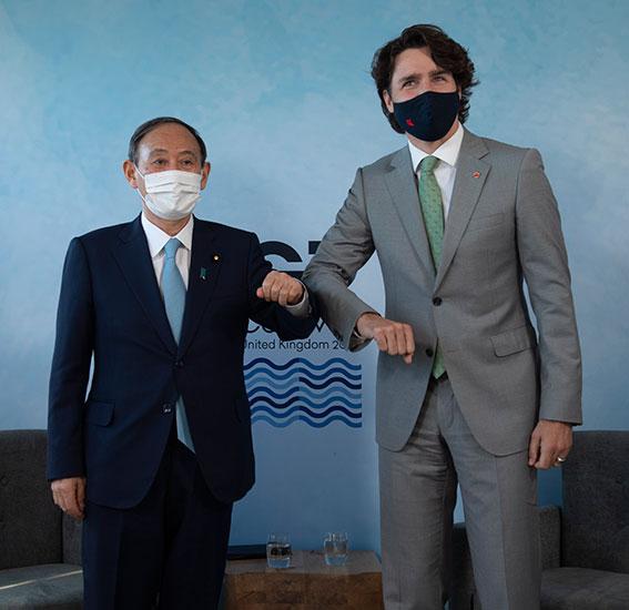 日本首相菅义伟(左)周日与加拿大总理特鲁多举行双边会谈。特鲁多表示,将派选手团参加东奥。(美联社)