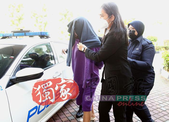 女嫌犯被押抵法庭时,其代表律师为不让其样貌曝光,立即以衣服遮盖在女嫌犯头上。