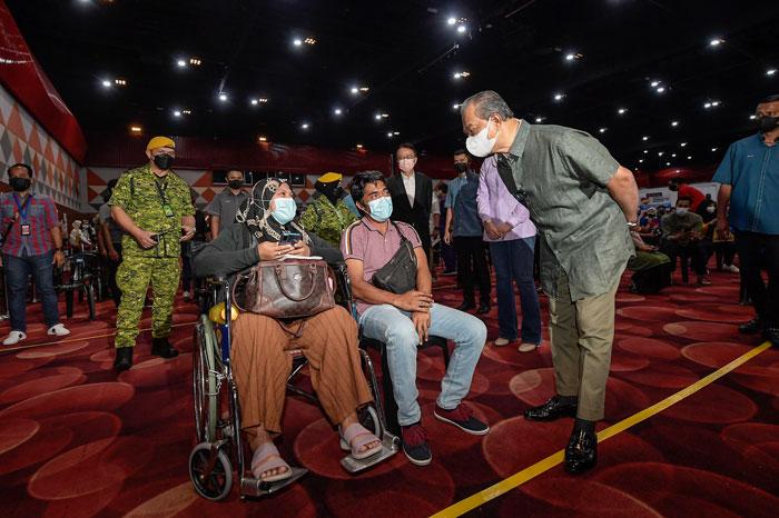 慕尤丁(右)问候坐轮椅前来接种疫苗的民众。