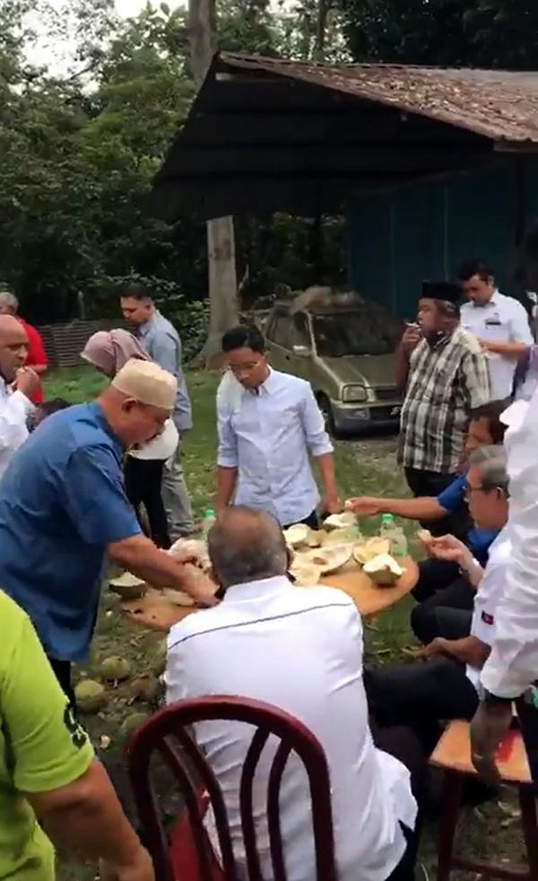 视频显示莫哈末拉昔(坐者右,身穿白衣)手拿榴梿品尝,其一名助理也在视频内,一般相信拍摄地点是在峇株巴辖。