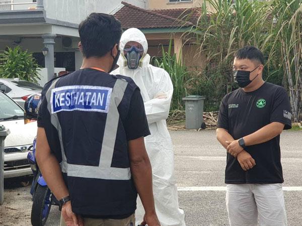 甲市区国会消毒工作队协助甲中央县卫生局,前往确诊患者的单位进行消毒工作,右为朱智威。