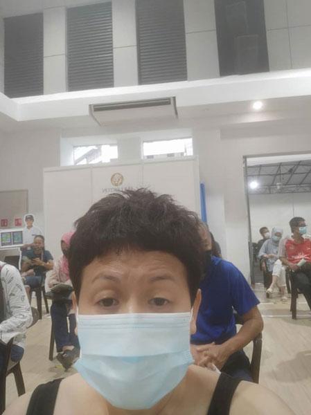 何嫦娥戴着口罩,到指定地点准备接种疫苗。