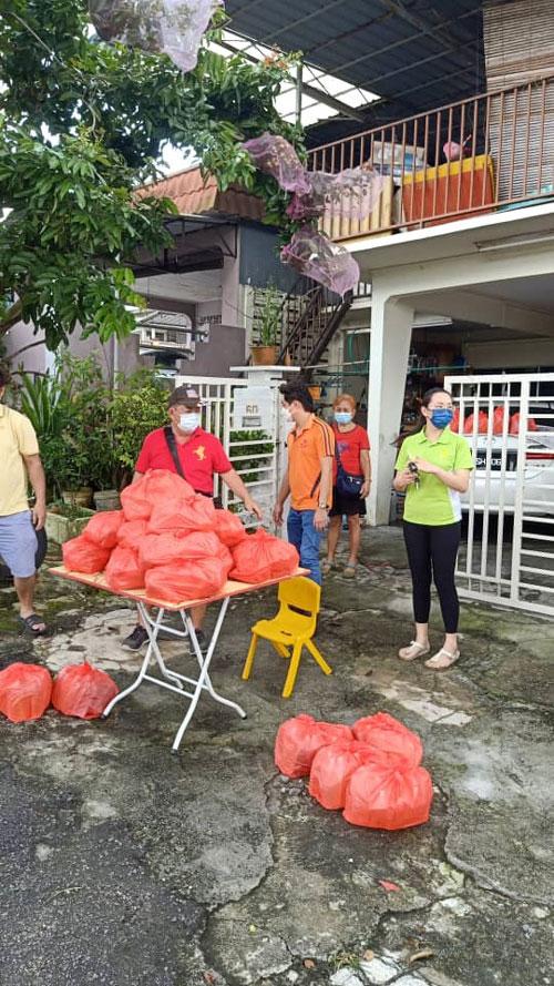戴南香(右3)获赞助人的捐献,派饭盒给有需要的人士。