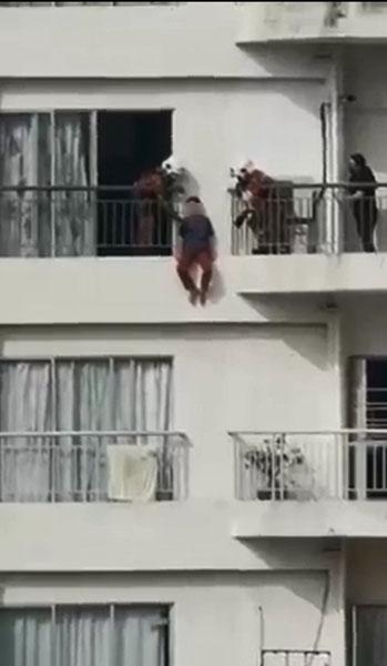 妇女坐在阳台外墙,似乎准备跳楼轻生。