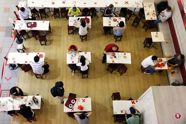 """允许五人聚餐意味着病毒在""""两层人际关系""""之内有125种传播途径。(《联合早报》档案照)"""