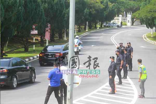 警员站在皇宫大门前,向路过的首相官车敬礼。