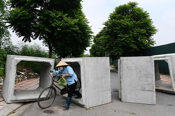 AFP 121014 河内当局设置路障封锁马路,有民众骑脚车从中穿过。(法新社)