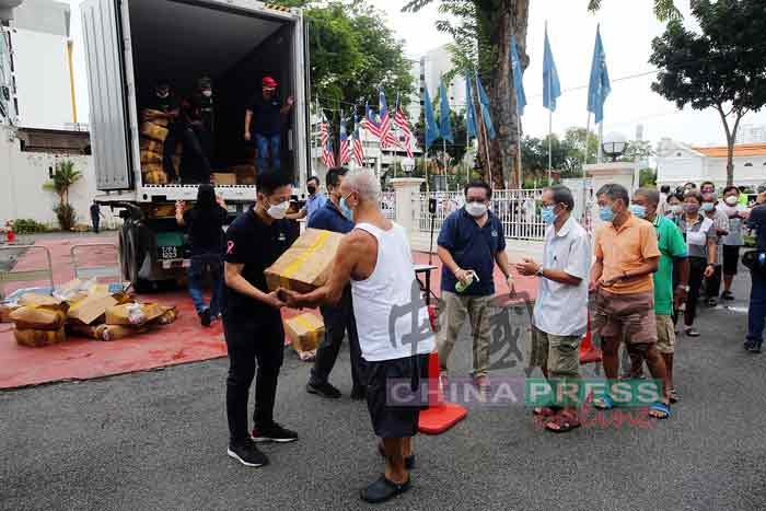 载满虾丸的一辆货柜停驻在民政党所内,胡栋强(左)派发一箱虾丸给民众。
