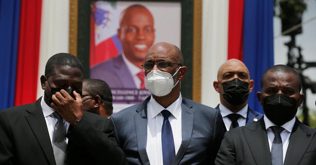 海地总统莫伊兹(相框中人)7月遭暗杀,检方指出新任总理亨利(中)曾和嫌犯两度通话,事后却未吐实,正寻求起诉。